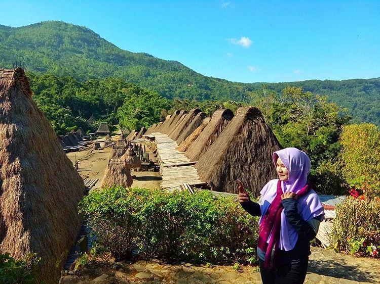Berfoto dengan latar rumah adat di kampung Bena, sumber ig @fitriihndyn_