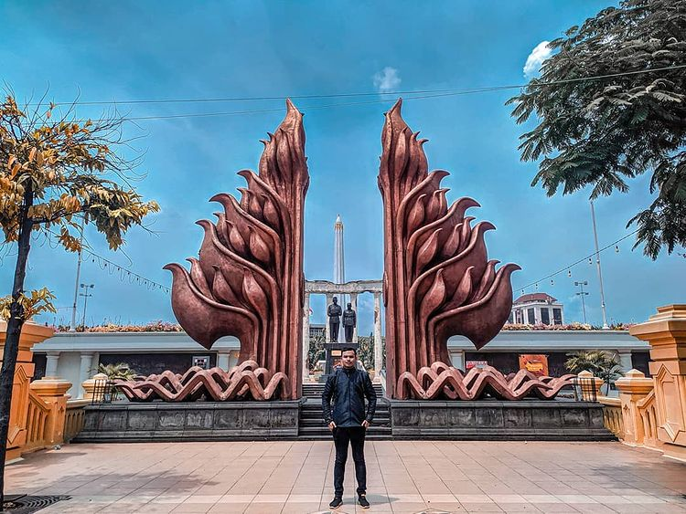 Pemuda berfoto di depan Tugu Pahlawan Surabaya, ig deni_namaku